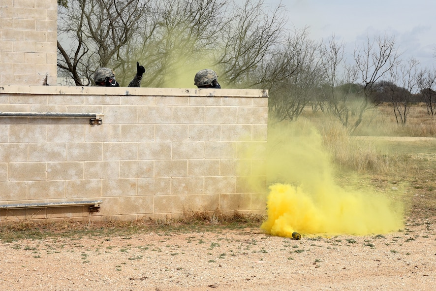 Students in the Warrior Ancillary Specialized Training Program check in with their wingmen through a smoke grenade during their final training exercise at the mock Forward Operating Base on Goodfellow Air Force Base, Texas, Feb. 28, 2018. During the final training exercise smoke grenades were used along with blank ammunition and simulated ground bursts. (U.S. Air Force photo by Airman 1st Class Hines/Released)