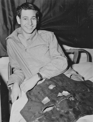 B-17 Flying Fortress radio operator Sgt. James Bothwell, smiles as he displays the back of the flak jacket that saved his life over Germany. He sustained only minor injuries. (U.S. Air Force photo)