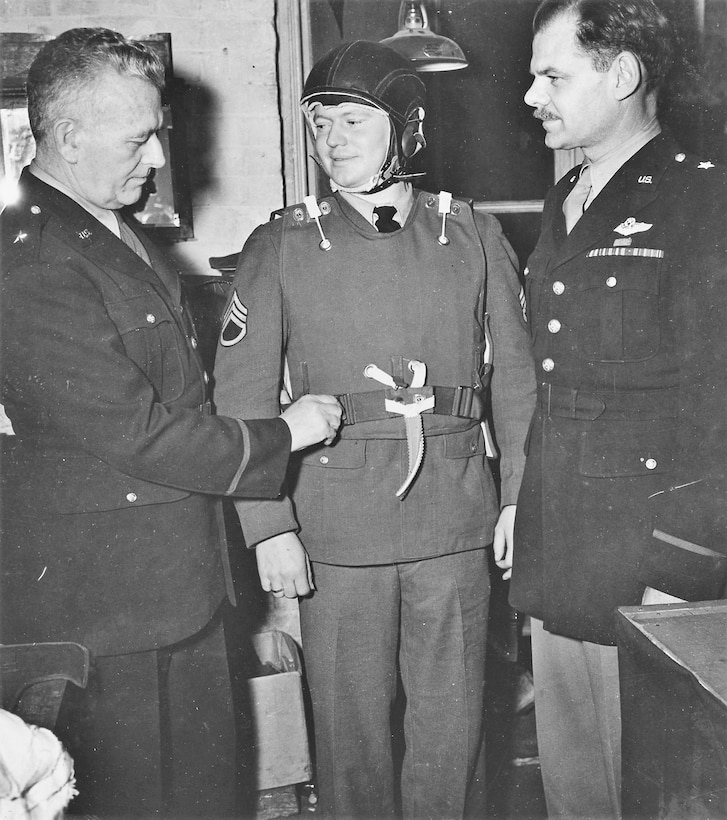 Brig. Gen. Malcolm C. Grow (left), designer of protective equipment for combat fliers, and Brig. Gen. Leon Johnson (right) look over a modified vest and new helmet worn by Staff Sgt. Ambrous T. Hansen (center), a gunner on a B-24 Liberator. (U.S. Air Force photo)