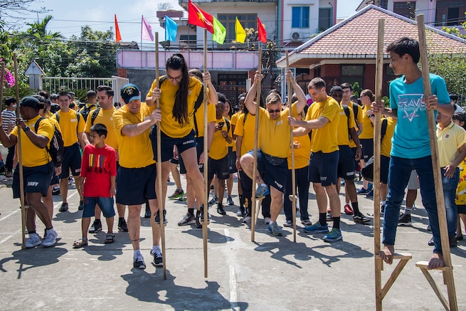 Sailors walk on stilts during a visit with children during a community event.