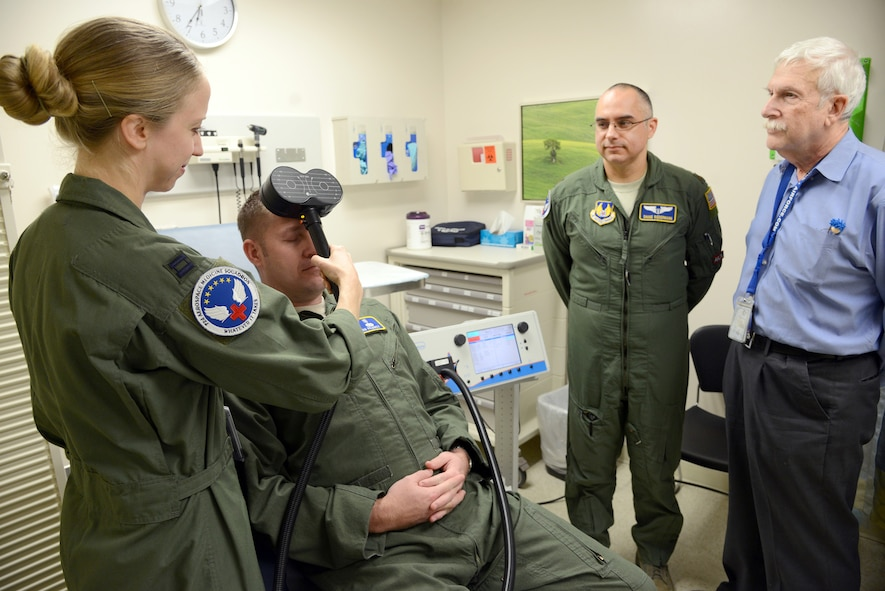 Dr. Stacy Zimmerman, an associate investigator, demonstrates using the Transcranial Magnetic Stimulation (TMS) on Capt. Josh Pearcy, a physician assistant, while Dr. Shane Biedermann and Dr. Harold Ginzburg observe. Biedermann, as the primary investigator, and his team, are looking for combat veteran volunteers with Post Traumatic Stress Disorder to participate in this noninvasive study using electroencephalography.