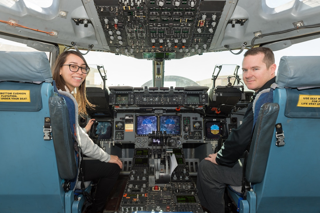 Karen Sanchez, Human Systems Integration engineer, and Matt Osburn, 418th Flight Test Squadron C-17 lead Engineer, sit in the cockpit of a C-17 Globemaster III with new Replacement Head-Up Displays installed for testing. (U.S. Air Force photo by Kyle Larson)