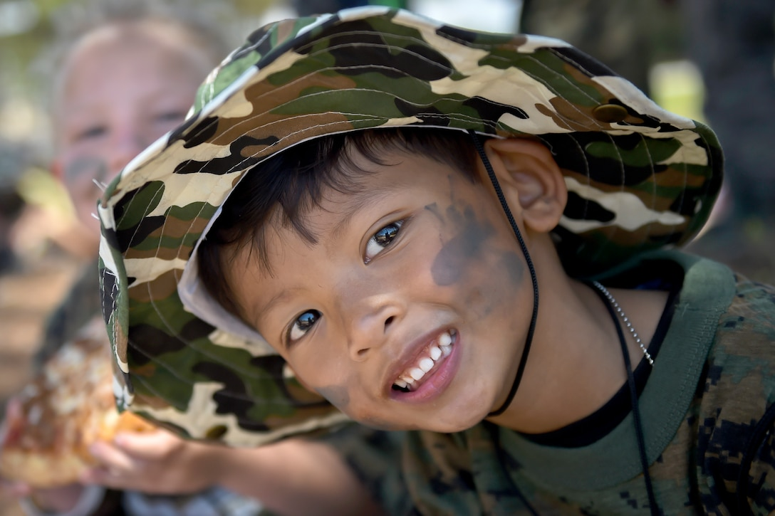 A child wearing a had and face paint poses for a photo.