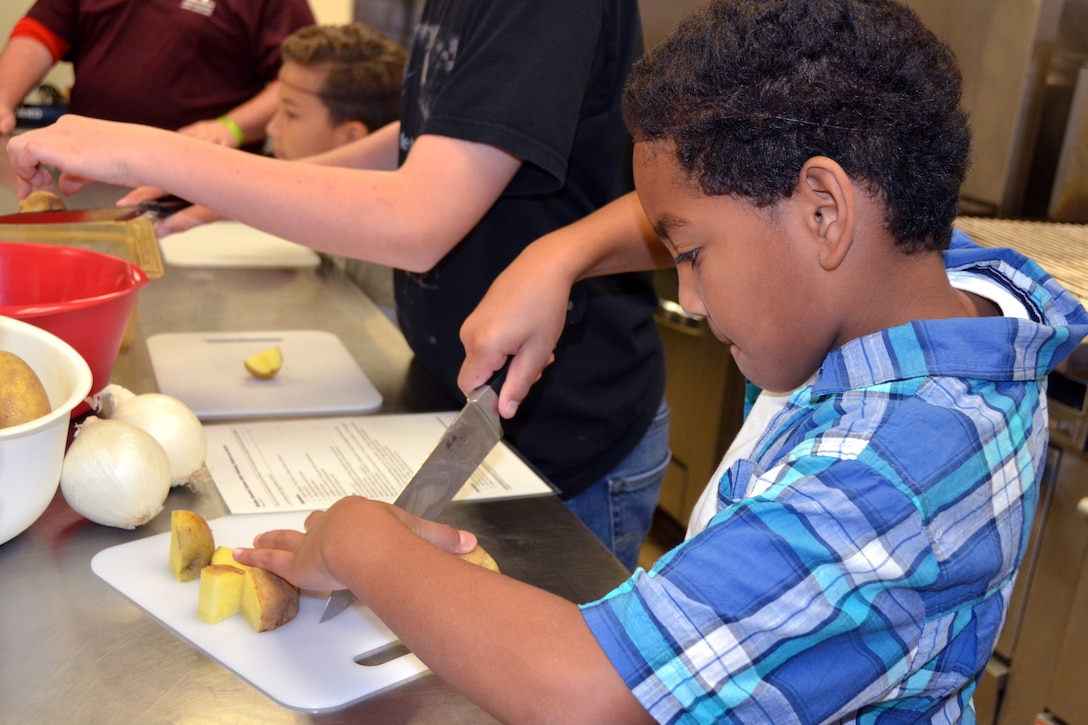 A child cuts potatoes with a knife.