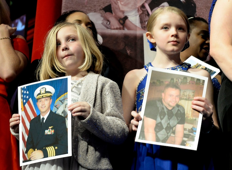 Family members hold photos of their fallen loved ones during the 10th Annual Tragedy Assistance Program for Survivors Honor Guard Gala March 6, 2018, in Washington, D.C. The program has helped more than 70,000 surviving family members cope with the devastating loss of loved ones. (U.S. Air Force photo by Staff Sgt. Rusty Frank)