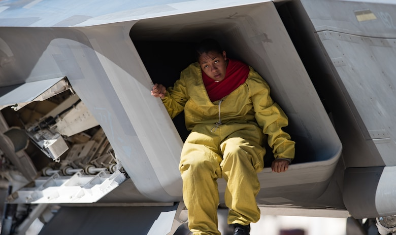 U.S. Air Force Tech. Sgt. Darshele Green, Air Combat Command Raptor Demostration Team avionics technician, climbs inside an F-22 Raptor's engine intake post-flight at the U.S. Air Force Heritage Flight Training Course at Davis-Monthan Air Force Base, Arizona, March 1, 2017.