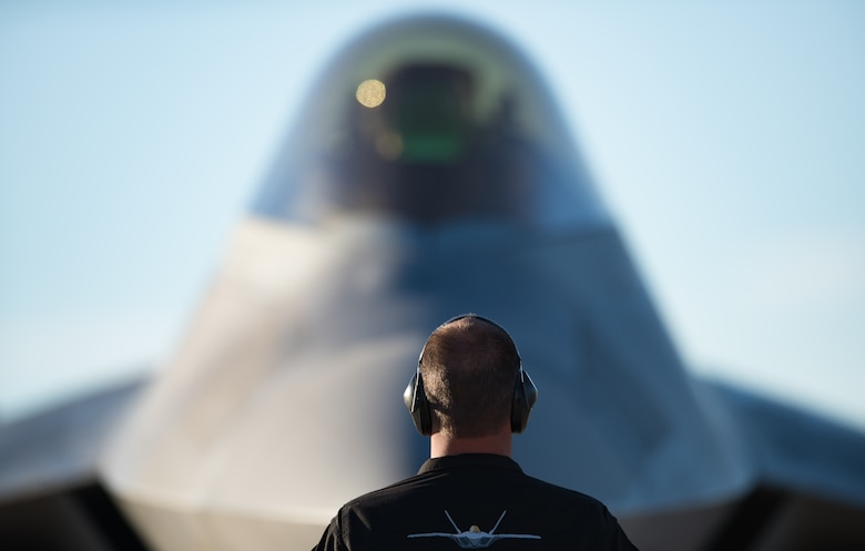 An Air Combat Command F-22 Raptor Demonstation Team crew chief directs parking an F-22 Raptor post-flight at the Heritage Flight Training Course at Davis-Monthan Air Force Base, Arizona, March 4, 2017.