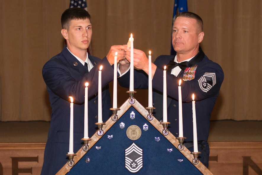 An Airman Basic and a chief master sergeant light the final candle on the ceremonial candelabrum during the Chief Recognition Ceremony at Luke Air Force Base, Ariz., March 3, 2018. The candles represented each of the nine enlisted ranks that an Airman must pass through before reaching chief. (U.S. Air Force photo/Senior Airman Ridge Shan)