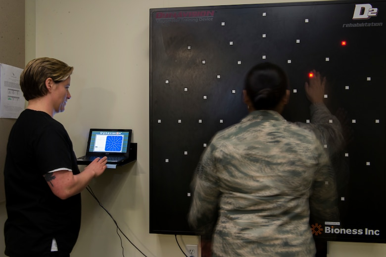 Dr. Deana Kubosh, Traumatic Brain Injury clinic occupational therapist, examines a patient using a Visuomotor training device at Joint Base Elmendorf-Richardson, Alaska, Feb. 26, 2018. This device is used for rehabilitation through the testing of motor and cognitive reaction speeds.
