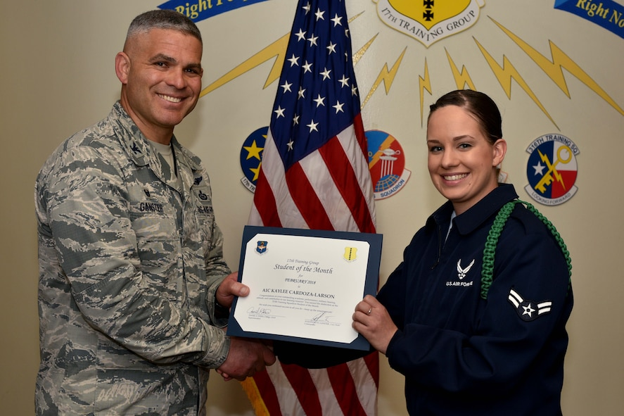 U.S. Air Force Col. Alex Ganster, 17th Training Group commander, presents the 17th TRG Student of the Month certificate to Airman 1st Class Kaylee Cardoza-Larson, 315th Training Squadron trainee, in Brandenburg Hall on Goodfellow Air Force Base, Texas, March 2, 2018. The 315th TRS's vision is to develop combat-ready intelligence, surveillance and reconnaissance professionals and promote an innovative squadron culture and identity unmatched across The U.S. Air Force. (U.S. Air Force photo by Senior Airman Randall Moose/Released)