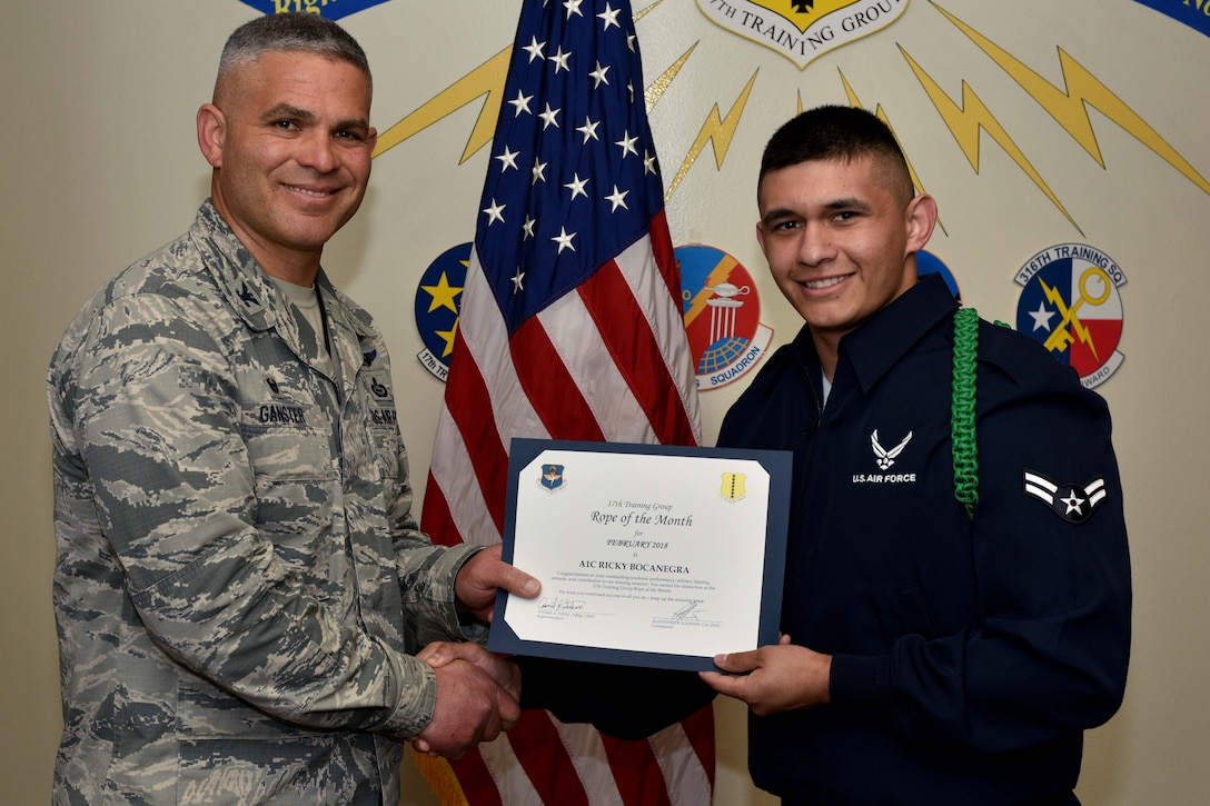 U.S. Air Force Col. Alex Ganster, 17th Training Group commander, presents the 17th TRG Rope of the Month certificate to Airman 1st Class Ricky Bocanegra, 315th Training Squadron trainee, in Brandenburg Hall on Goodfellow Air Force Base, Texas, March 2, 2018.  The mission of the 17th TRG is to train, develop and inspire professional fire protection and intelligence, surveillance and reconnaissance warriors. (U.S. Air Force photo by Senior Airman Randall Moose/Released)