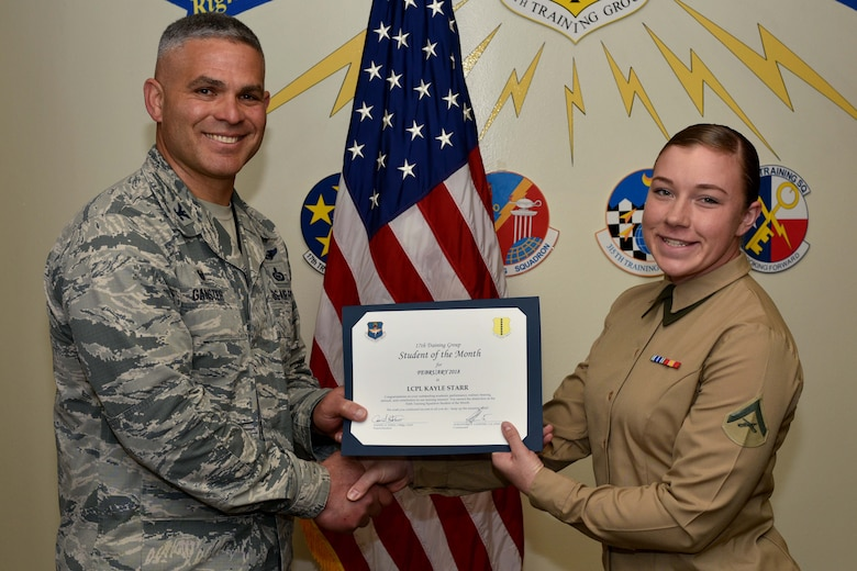 U.S. Air Force Col. Alex Ganster, 17th Training Group commander, presents the 17th TRG Student of the Month certificate to U.S. Marine Corps Lance Cpl. Kayle Starr, 316th Training Squadron trainee, in Brandenburg Hall on Goodfellow Air Force Base, Texas, March 2, 2018. The 316th TRS's mission is to conduct U.S. Air Force, U.S. Army, U.S. Marine Corps, U.S. Navy and U.S. Coast Guard cryptologic, human intelligence and military training.  (U.S. Air Force photo by Senior Airman Randall Moose/Released)