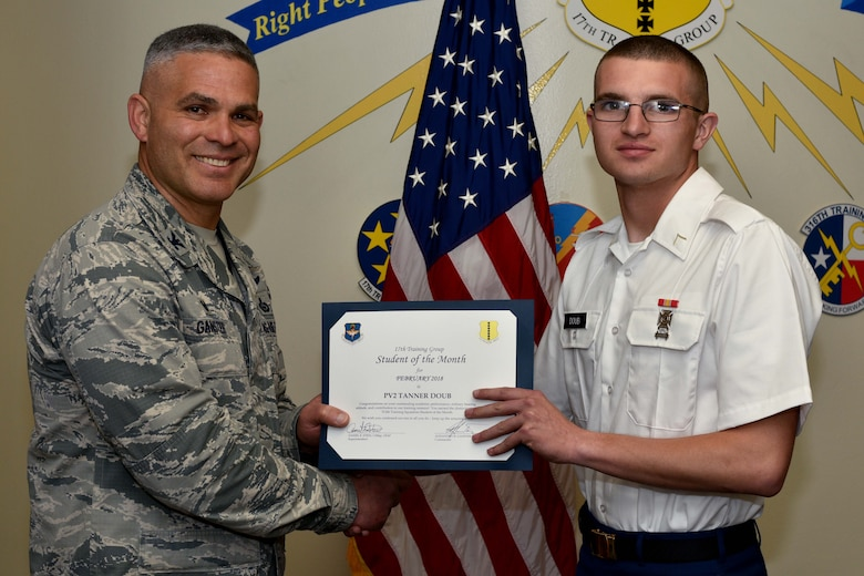 U.S. Air Force Col. Alex Ganster, 17th Training Group commander, presents the 17th TRG Student of the Month certificate to U.S. Army Private 2nd Class Tanner Doub, 312th Training Squadron trainee, in Brandenburg Hall on Goodfellow Air Force Base, Texas, March 2, 2018.  The 312th TRS's mission is to provide Department of Defense and international customers with mission ready fire protection and special instruments graduates and provide mission support for the Air Force Technical Applications Center. (U.S. Air Force photo by Senior Airman Randall Moose/Released)