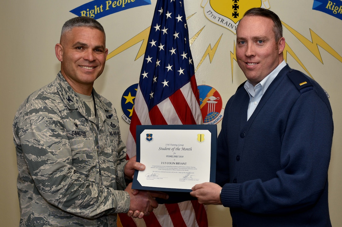 U.S. Air Force Col. Alex Ganster, 17th Training Group commander, presents the 17th TRG Student of the Month certificate to 2nd Lt. Colin Bryant, 315th Training Squadron trainee, in Brandenburg Hall on Goodfellow Air Force Base, Texas, March 2, 2018. The 315th TRS's vision is to develop combat-ready intelligence, surveillance and reconnaissance professionals and promote an innovative squadron culture and identity unmatched across The U.S. Air Force. (U.S. Air Force photo by Senior Airman Randall Moose/Released)
