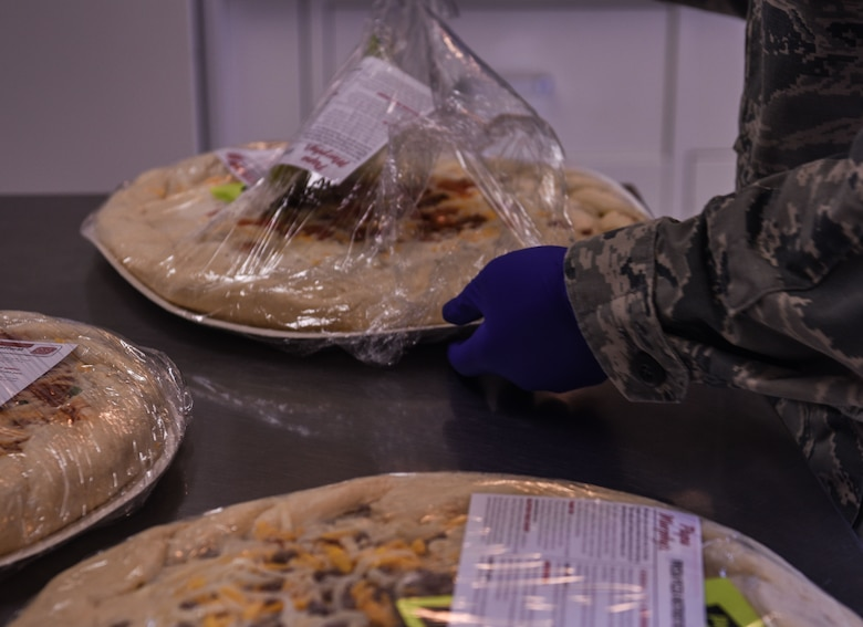 Airman 1st Class Kathleen Reynolds, 90th Force Support Squadron missile chef, prepares a pizza for the Airmen working at a missile alert facility March 3, 2018, in the F.E. Warren Air Force Base missile complex. As the sole chef at a MAF, Reynolds is responsible for feeding the Airmen stationed with her for every meal, no matter the time of day. (U.S. Air Force Photo by Airman 1st Class Braydon Williams)