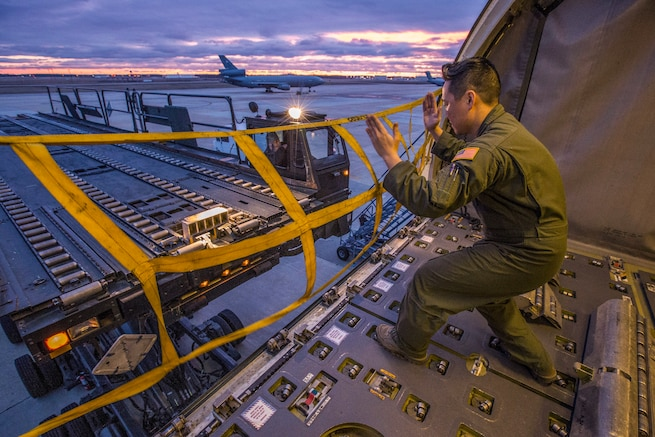 An airman uses his hands to signal the operator of an aircraft loadr/transporter.