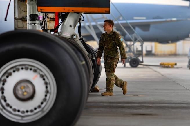 An airman conducts pre-flight checks on a KC-10 Extender aircraft.
