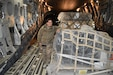 U.S. Army Staff Sgt. Bina K. Cheema stands with packaged Microwave Line-of-Sight radios aboard a C-17 Globemaster III.