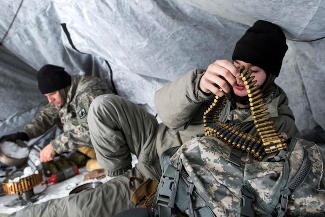 A soldier prepares an ammo belt.