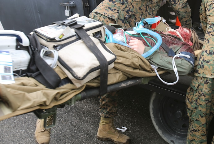 A U.S. service member is loaded onto an aircraft after being stabilized by Navy doctors and hospital corpsmen with 2nd Medical Battalion, 2nd Marine Logistics Group, during a certification exercise at Camp Lejeune, N.C., March 1, 2018. The exercise was designed for shock trauma platoons and forward resuscitation surgical units to ensure the unit sustains medical proficiency and is capable of handling emergencies in future deployments.