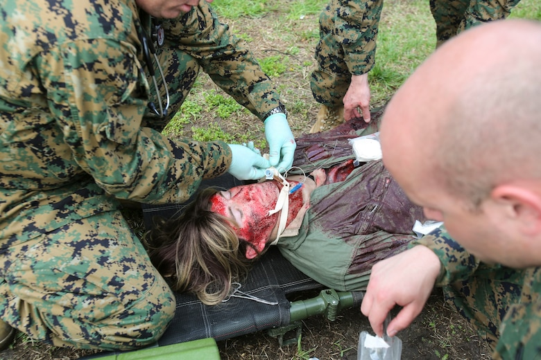 U.S. Navy doctors and hospital corpsmen with 2nd Medical Battalion, 2nd Marine Logistics Group, simulate opening the airway of a wounded service member during a certification exercise at Camp Lejeune, N.C., March 1, 2018.  The exercise was designed for shock trauma platoons and forward resuscitation surgical units to ensure medical proficiency in handling emergencies in future deployments.