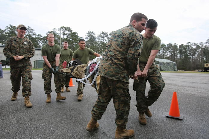 U.S. Navy doctors and hospital corpsmen with 2nd Medical Battalion, 2nd Marine Logistics Group, simulate loading a wounded service member onto an aircraft for a medical evacuation during a certification exercise at Camp Lejeune, N.C., March 1, 2018.  The exercise was designed for shock trauma platoons and forward resuscitation surgical units to ensure the unit sustains medical proficiency and is capable of handling emergencies in future deployments.