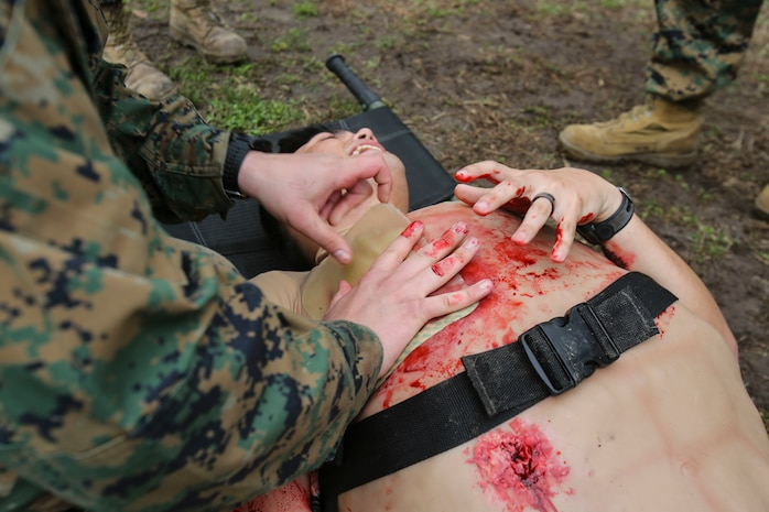 A U.S. Navy hospital corpsman with 2nd Medical Battalion, 2nd Marine Logistics Group, simulate applying a chest seal to a gunshot wound on a rubber suit used for training during a certification exercise at Camp Lejeune, N.C., March 1, 2018. The exercise was designed for shock trauma platoons and forward resuscitation surgical units to ensure the unit sustains medical proficiency and is capable of handling emergencies in future deployments.