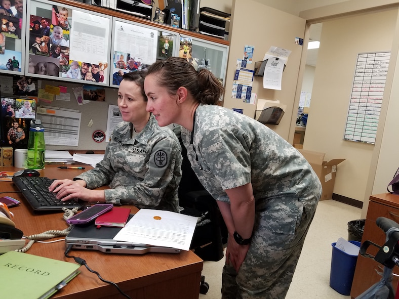 Dr. Cassandra Kerwin (seated) and Dr. Jessica Clarkson reviewing some information for upcoming appointments. (U.S. Air Force photo/Laura McGowan)