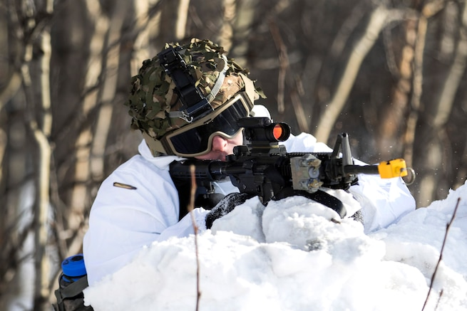 A soldier fires blank rounds during cold weather survival training.
