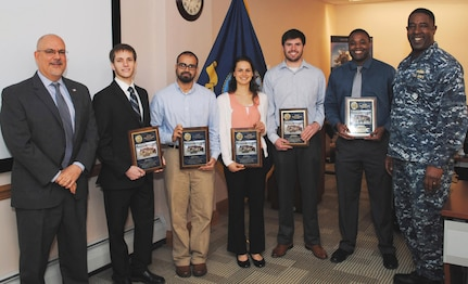 IMAGE: DAHLGREN, Va. (Feb. 26, 2018) - Five members of the Naval Surface Warfare Center Dahlgren Division (NSWCDD) Sly Fox Mission 22 team - Michael Parkison, Jamshaid Chaudhry, Michelle Craft, Joseph Gills, and Allen Woods - hold the Sly Fox Awards they received from NSWCDD Commanding Officer Capt. Godfrey 'Gus' Weekes and NSWCDD Technical Director John Fiore at the command's leadership meeting. They were among seven Sly Fox Mission 22 members honored for developing a rapid prototyping technology called the Collaborative Aerial Network for the Autonomous Remote Engagement System (CANARES) - fully integrated with an unmanned aerial vehicle (UAV), an unmanned ground vehicle, and a command and control station. The unmanned vehicle - dubbed the Weaponized Autonomous System Prototype (WASP) - was integrated by the team with a UAV to provide an aerial perspective for increased situational awareness. Navy civilian and military personnel witnessed the Mission 22 demonstration of CANARES as it quickly and effectively detected, tracked, and engaged target after target on the Potomac River Test Range at a September demonstration. For more news and information on CANARES technology and its demonstration, the full story - U.S. Navy Mission 22 Team Develops 'Game Changing' Unmanned Capability - is available via this link: http://www.navsea.navy.mil/Media/News/Article/1369371/us-navy-mission-22-team-develops-game-changing-unmanned-capability.  (U.S. Navy photo by Bill Tremper/Released)