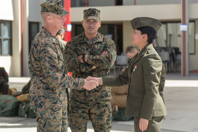 U.S. Marine Col. Jeffery Holt, commanding officer, School of Infantry - West, and Sgt. Maj. Jonathon Groth, School of Infantry - West sergeant major, greets Pvt. Nathalie Lizama. She is the second female to arrive at SOI - W on Camp Pendleton, Calif., March 6, 2018. This marks the first male-female integrated Marine Combat Training company on the West Coast.