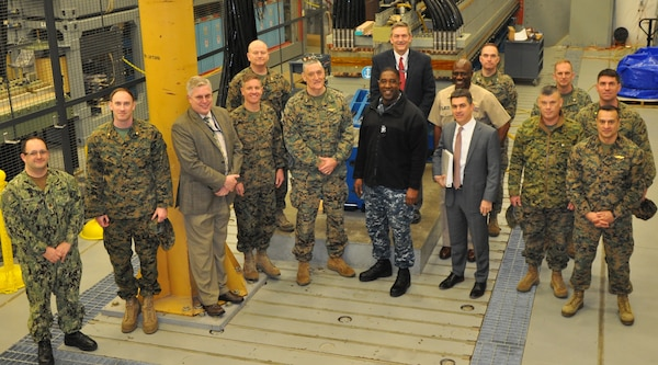 IMAGE: DAHLGREN, Va. (Feb, 23, 2018) - U.S. Marine Corps officers led by Maj. Gen. David Coffman, center, and pictured to his left, Brig. Gen. Matt Trollinger, join Capt. Godfrey 'Gus' Weekes, Naval Surface Warfare Center Dahlgren Division (NSWCDD) commanding officer, center next to Coffman, and NSWCDD leadership in front of the Navy's electromagnetic railgun prototype launcher. NSWCDD engineers briefed the Marine Corps leaders on electromagnetic launchers, hypervelocity projectiles, directed energy weapons, unmanned autonomous systems, and the 155mm moving target artillery round. The Marines saw NSWCDD facilities and the command's capability to develop and integrate complex warfare systems, including the ability to incorporate electric weapons technology into existing and future fighting forces and platforms. Coffman is the director of the U.S. Navy Expeditionary Warfare Division. Trollinger is the Operations Division director for Plans, Policies, and Operations at U.S. Marine Corps Headquarters. Dale Sisson, NSWCDD deputy technical director, is pictured to Weekes' right. Tom Boucher, Office of Naval Research Railgun Program manager, is pictured to the left of Trollinger. Chester Petry, NSWCDD electromagnetic railgun lead systems engineer, stands center back row.