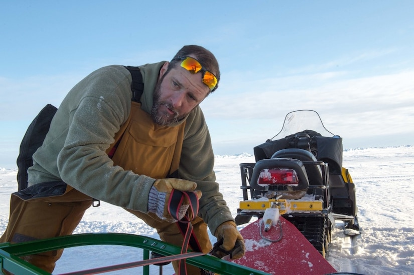 A research professor with the University of Alaska Fairbanks, prepares supplies for transport to Ice Camp Skate during the Navy's Ice Exercise 2018 in the Arctic Circle.