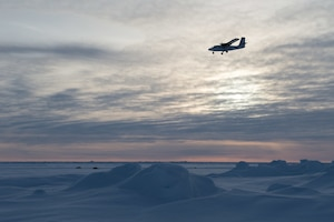 A Royal Canadian Air Force DHC-6 Twin Otter aircraft delivering supplies and personnel flies over an ice floe during Ice Exercise 2018 in the Arctic Circle.