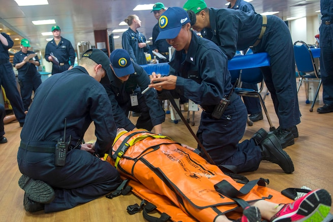 Sailors assess and prepare to transport a mock trauma patient.
