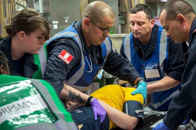 Sailors assess a simulated trauma patient during a mass casualty drill.