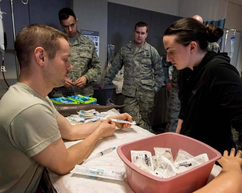 Capt. Neal Alexander, maternal child flight manager at the 92nd Medical Group, shows Airman 1st Class Jessica Schiller, an aerospace medical service apprentice at the 141st Medical Group, where to check for expiration dates on medical supplies during IV and laboratory draw training March 4, 2018 at the simulation lab at the Washington State University College of Nursing Riverpoint Campus in Spokane, Wash. More than 45 nurses, medics and medical providers from the 141st MDG as well as seven medical personnel assigned to the 92nd MDG teamed up for the combined training during March's unit training assembly. (U.S. Air National Guard photo by Staff Sgt. Rose M. Lust)