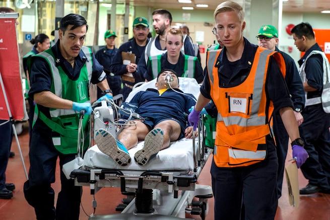U.S. sailors move a simulated trauma patient.