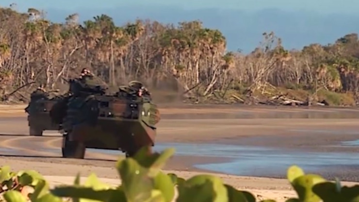 Amphibious vehicles drive along a beach.