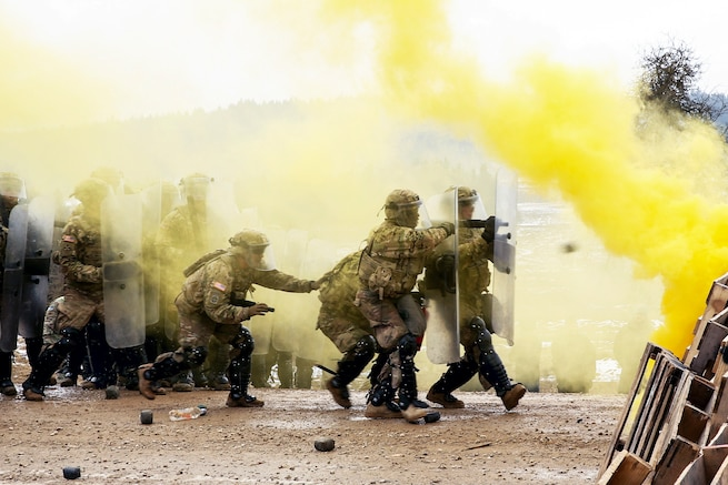 Soldiers conduct riot control training with shields as yellow smoke rises.