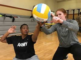 A volunteer sitting volleyball coach, helps a player with her float serve during practice for the Army Trials at Fort Bliss, Texas.
