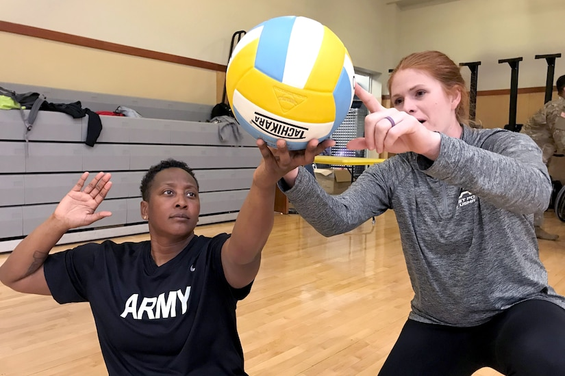 One person help another person holding a volleyball.