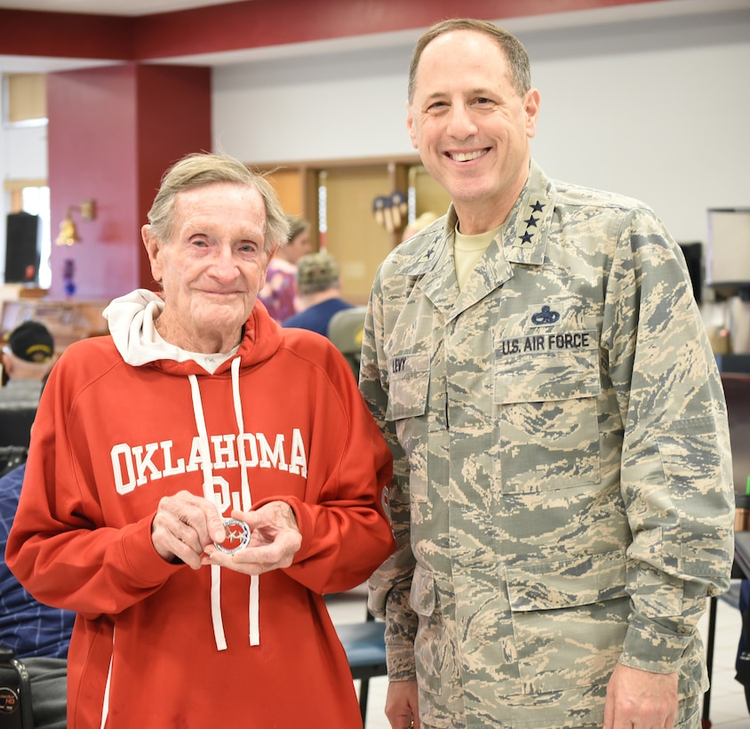 """Norman Veterans Center resident Allen Vann shows off the challenge coin he received from Air Force Sustainment Center Commander Lt. Gen. Lee K. Levy II Feb. 28, 2018, in Norman, Oklahoma.  Mr. Vann was recognized for being named """"2018 King of the Center"""" and turning 100 years old this year."""
