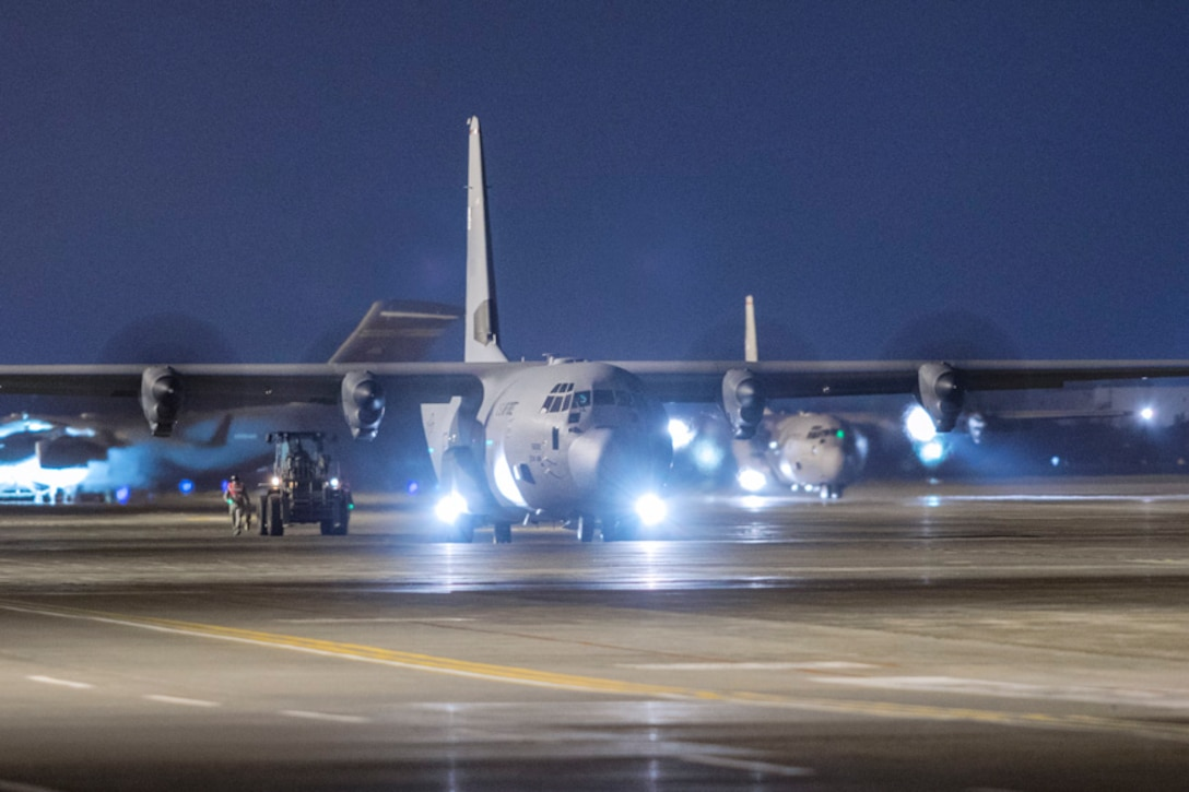 Airmen with the 374th Logistics Readiness Squadron combat mobility flight offload cargo from a C-130J Super Hercules
