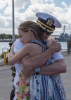 Cmdr. Chad Hardt, commanding officer of the Los Angeles-class fast attack submarine USS Tucson(SSN 770), is greeted by his daughter on the pier at Joint Base Pearl Harbor-Hickam after returning from a six-month Western Pacific deployment, Mar. 7.