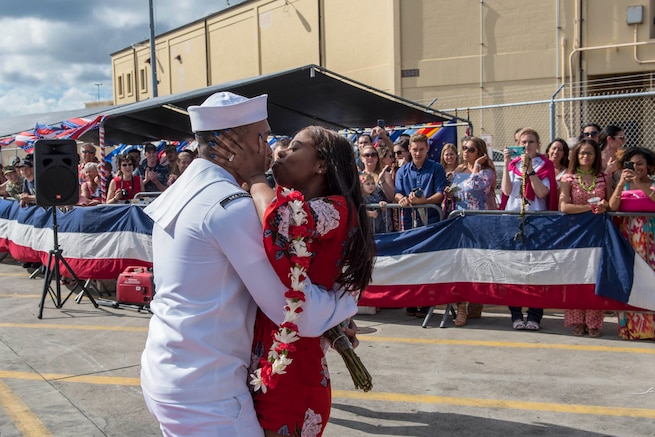 A sailor returning from a deployment embraces a loved one holding a lei as a crowd watches.