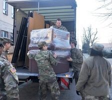 Army Capt. Jason M. Spalding, top center, 21st Theater Sustainment Command liaison officer, Mission Command Element, helps unload furniture at the Morale, Welfare and Recreation building in Poznan, Poland, Feb. 13, 2018. Spalding has transported large quantities over the last few months throughout the Atlantic Resolve area of operations to improve service members' quality of life. Army photo by Staff Sgt. Scott J. Evans