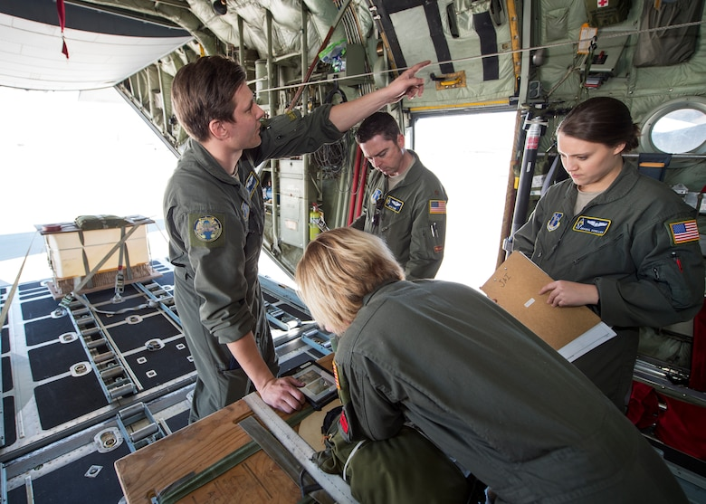 U.S. Air Force Staff Sgt. Timothy Hemquist (left), a load master with the 109th Airlift Squadron, goes through a preflight checklist in Yuma, Ariz., Feb. 28, 2018.