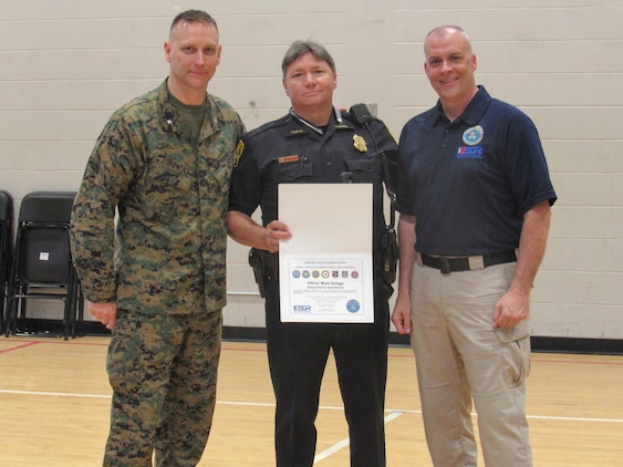 Lt. Col. Sean Zukowsky (left), commanding officer of 4th Assault Amphibian Battalion, 4th Marine Division, Marine Forces Reserve, and Dale Hoffman (right), volunteer at the Employer Support of the Guard and Reserve, present officer Mark Delage (center) with a letter of appreciation for his support to the Reserve Force members on March 2, 2018, in Tampa Fla.