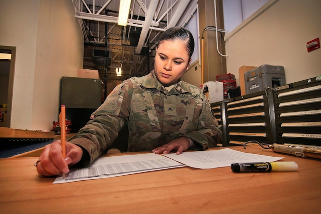 A soldier completes a supply request form.
